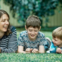 mother and sons laying on grass